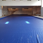 Indoor pool with a 20'x80' hydraulic cover system, royal blue cover with tracks mounted on top of deck