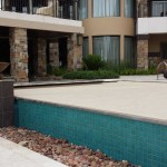 Recessed automatic pool cover system on an infinity edge pool