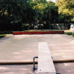 Above ground pool cover with a redwood bench housing the mechanism
