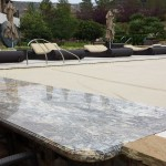 Custom granite counter top hides the pool cover system