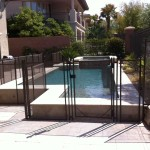 4' tall brown fence following the shape of the pool stepping up over a rock